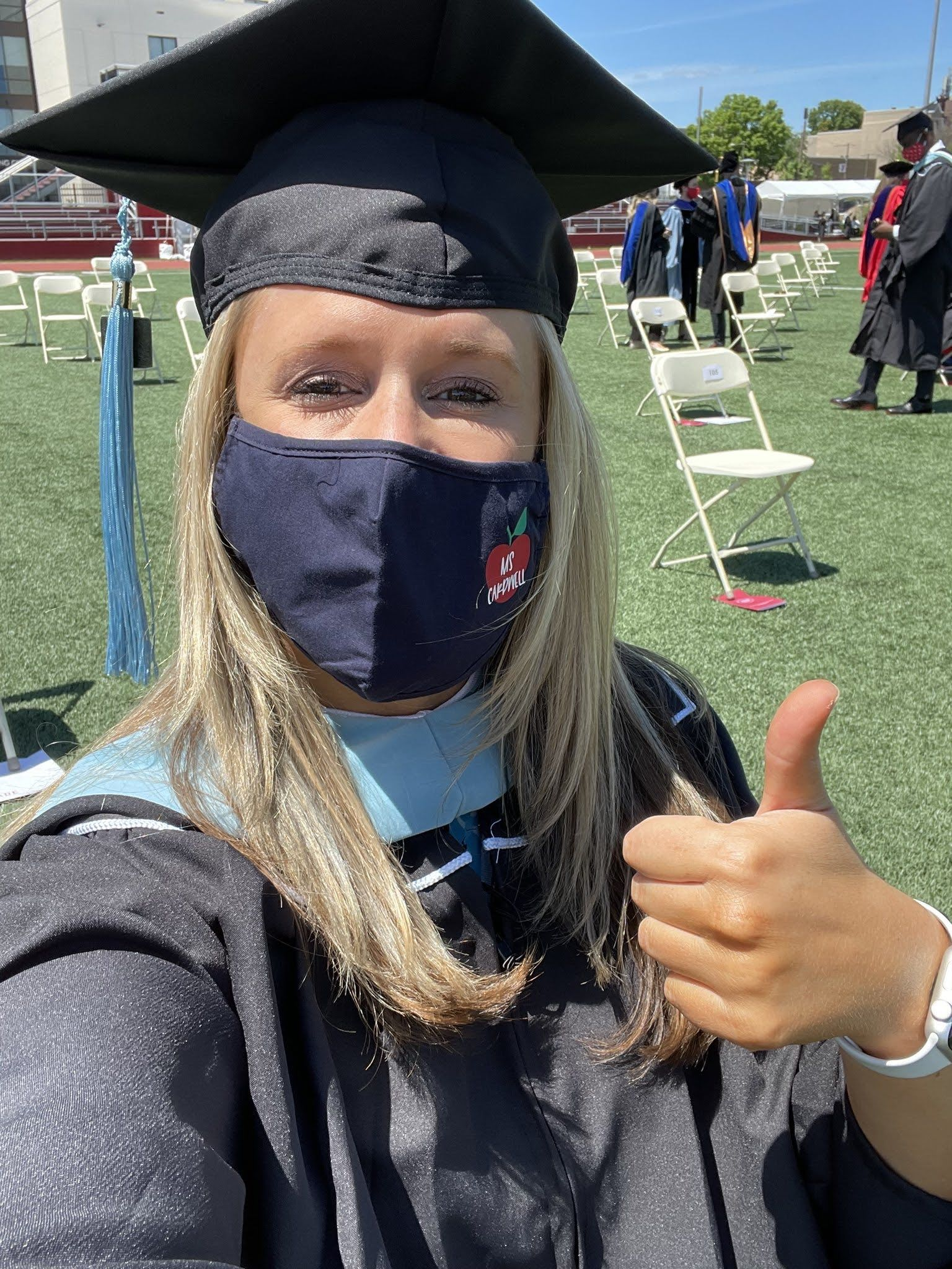 graduate gives a thumbs up