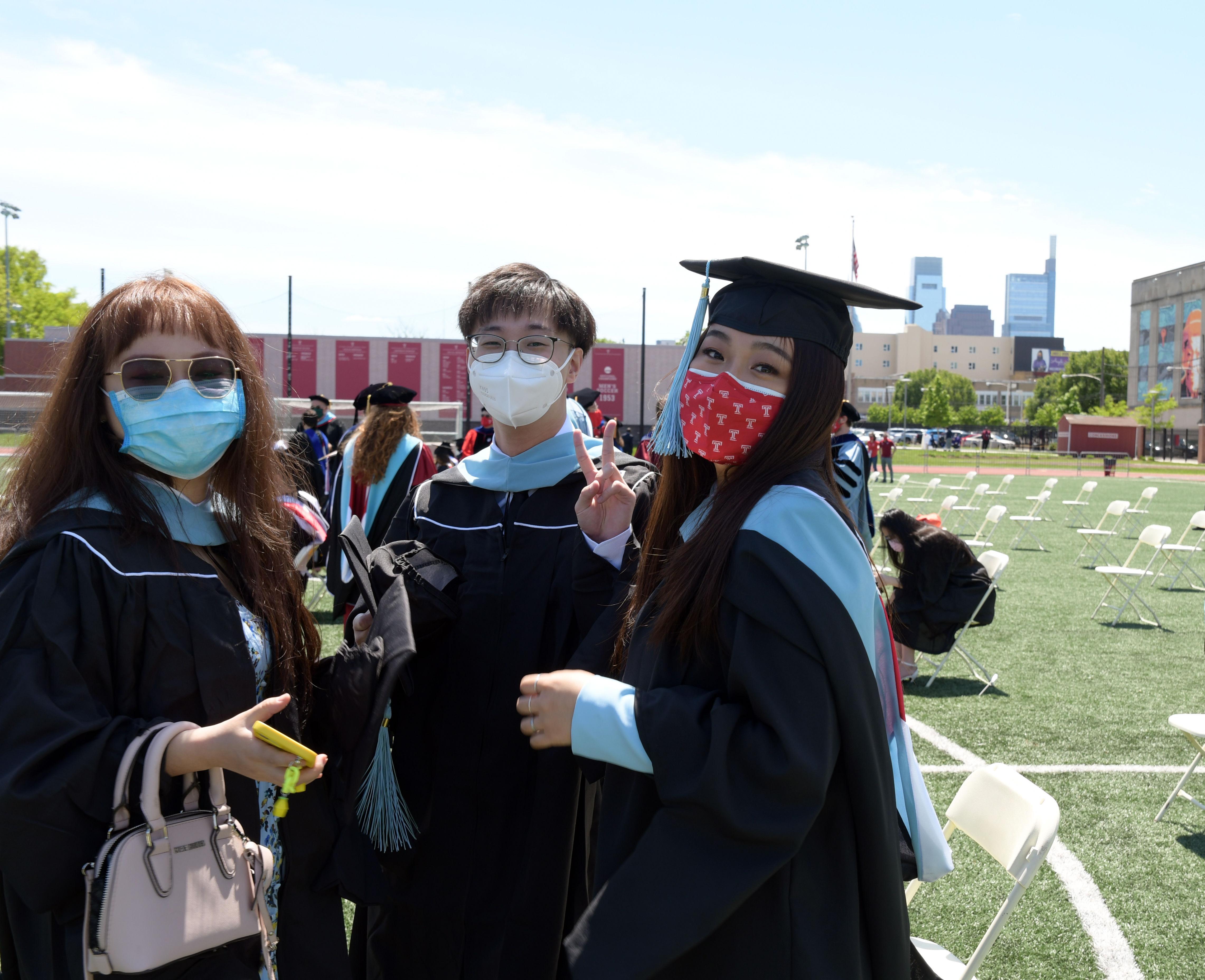 three graduates pose for photo