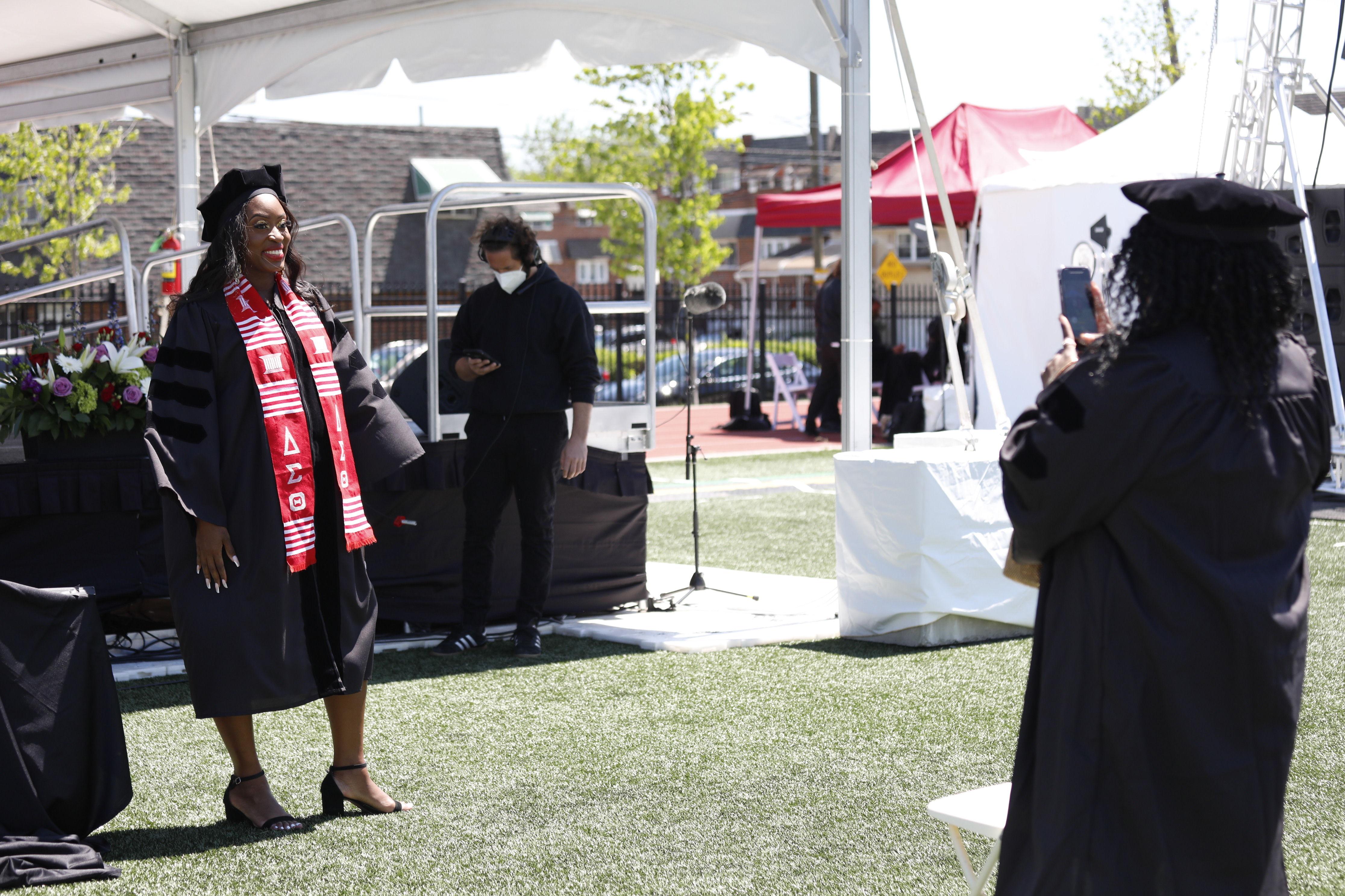 graduate poses on field