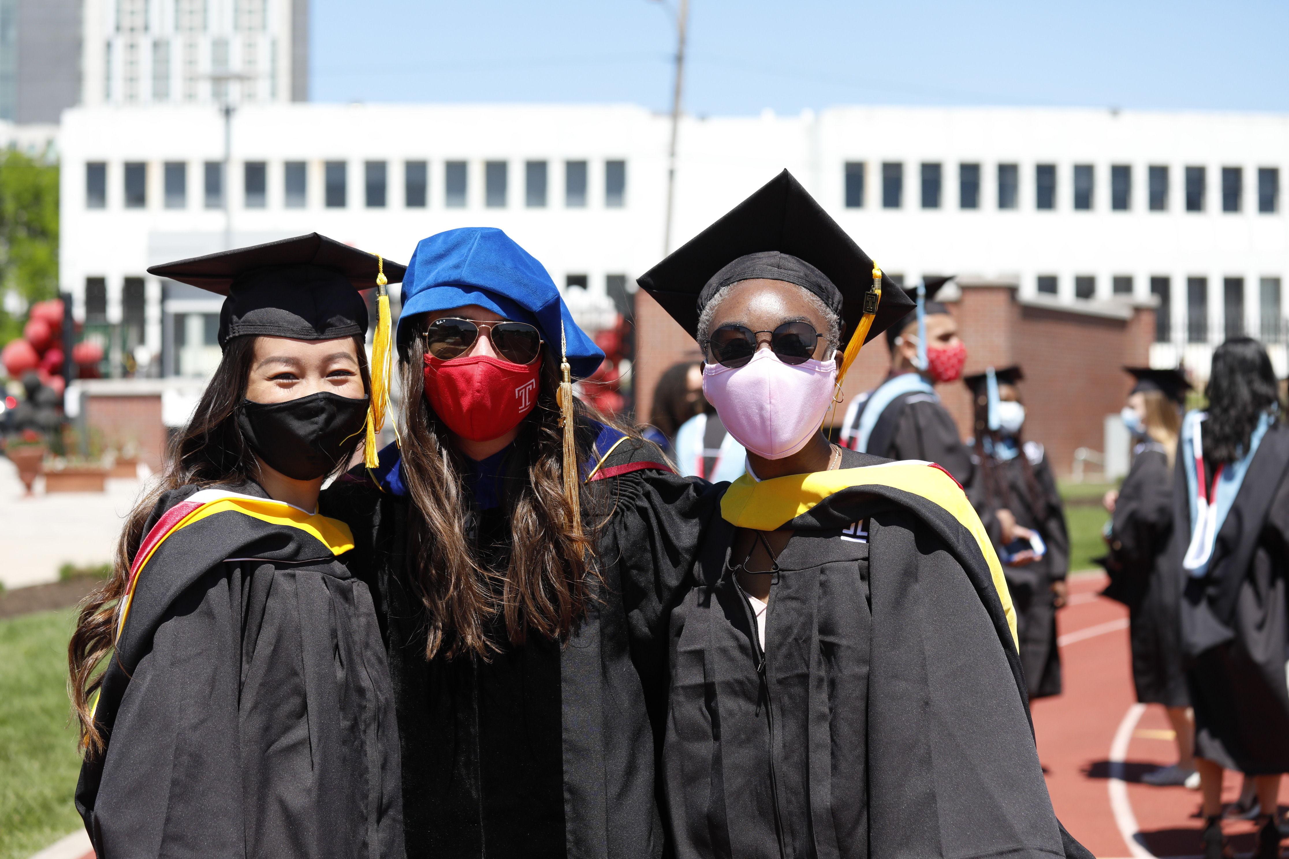 two graduates pose with professor