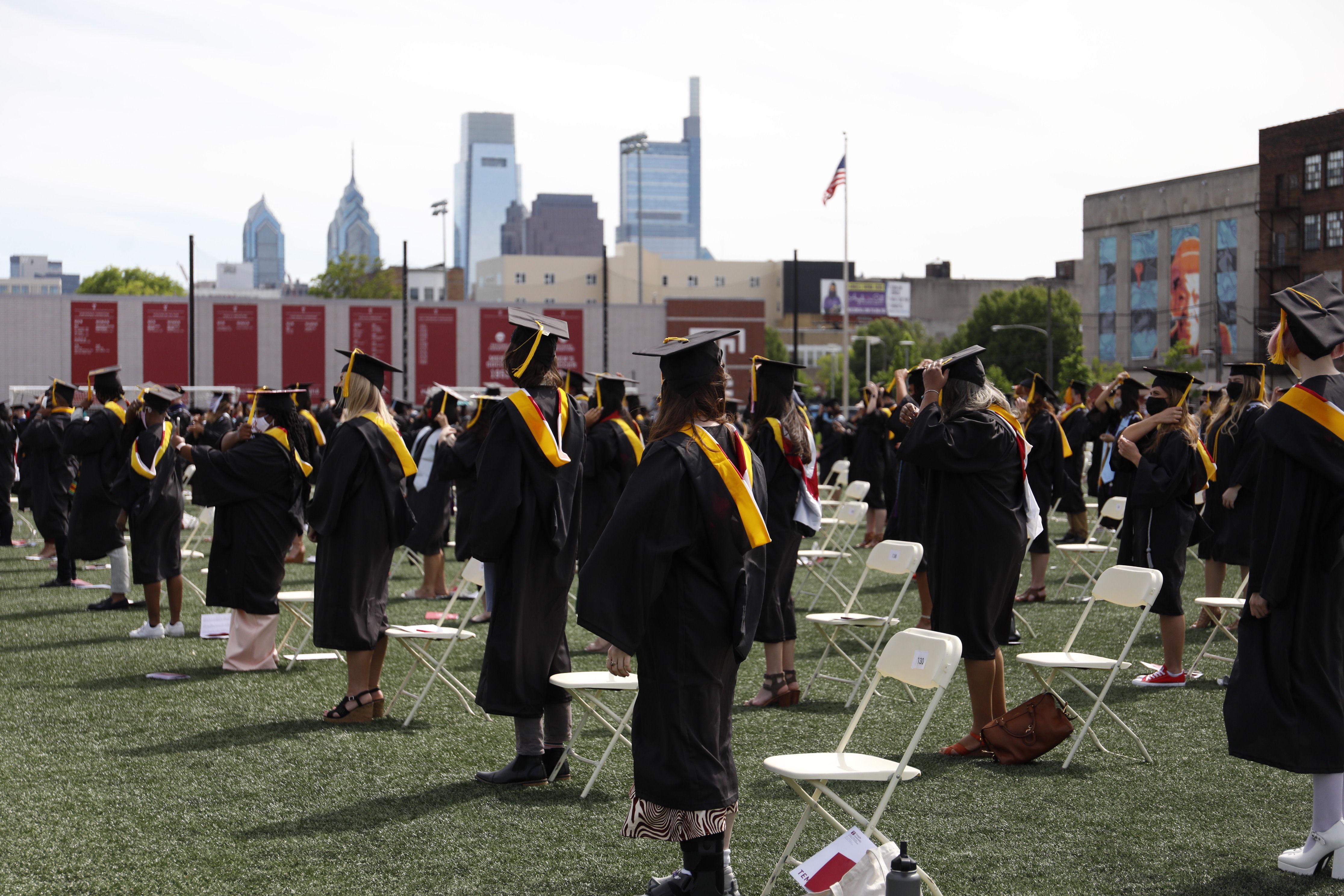 graduates stand on field