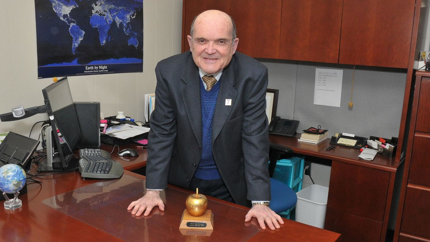 Joseph DuCette standing in his office at a desk with apple trophy on desk