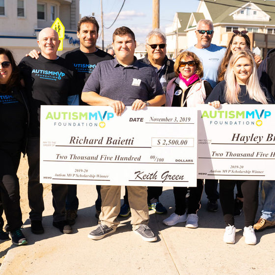 Autism MVP Foundation members pose with check