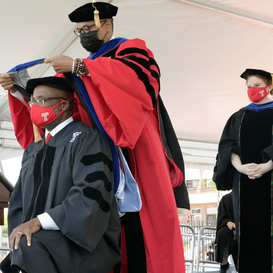 Doctoral graduate kneeling to be hooded by professor on stage